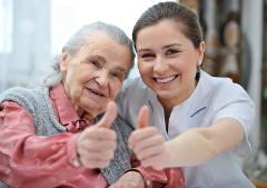 Senior mit der Pflegekraft mit OK-Zeichen